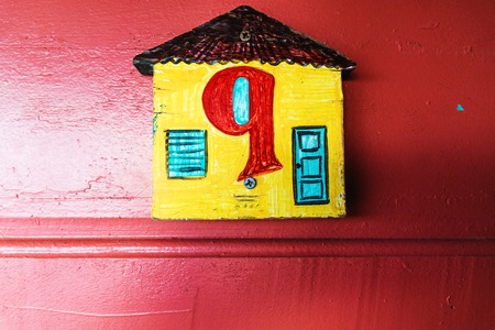 Number nine with arabic letters and maya letters in a yellow house with red wooden wall, Belize