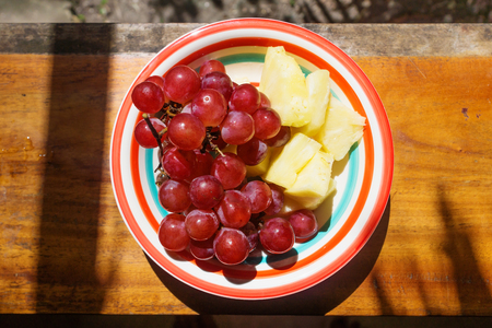 Fresh red grapes and yellow pineapple slices on colored plate, Guatemala