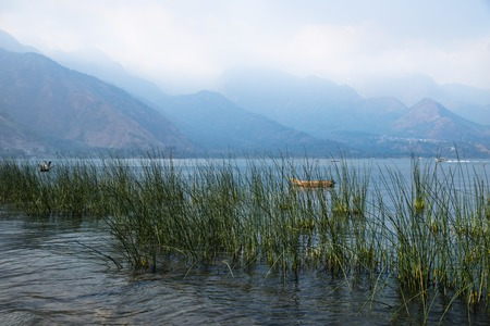 Canoe behind reed with misty volcanic mountains at Lago Atitlan, San Juan la Laguna, Guatemala, Central America
