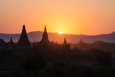 Silhouettes of Burmese Pagodas while sun is setting in the mountains from the view of Shwesandaw Pagoda, Bagan, Myanmar
