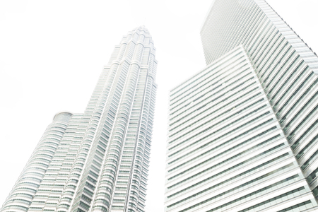 One of the Petronas Twin Towers and skyscraper from low angle view on a grey cloudy day, Kuala Lumpur, Malaysia Фото со стока