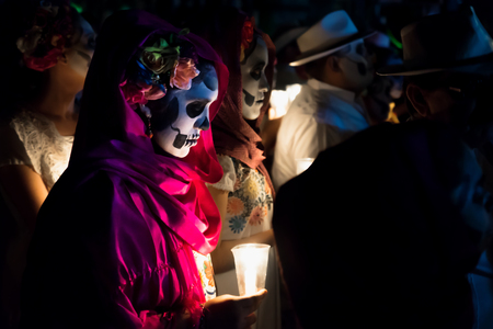 Merida, Cementerio General, Mexico - 31 October 2018: Close up of customed women dressed as Catrinas with skull make-up holding candles at the procession and parade for dia de los muertos at the Festival Des Las Animas