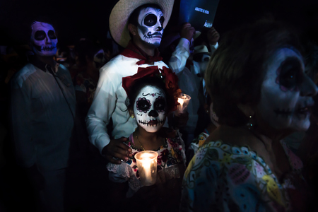 Merida, Cementerio General, Mexico - 31 October 2018: Customed participants of the parade with skull make-up, with a cowboy man and kid with flowers and heart paintings in her face holding candles at the parade for dia de los muertos at the Festival Des L