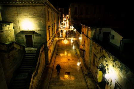 Silhouttes walking along the chrismas decorated cobbled streets of Zadar at night, Croatia, Europe