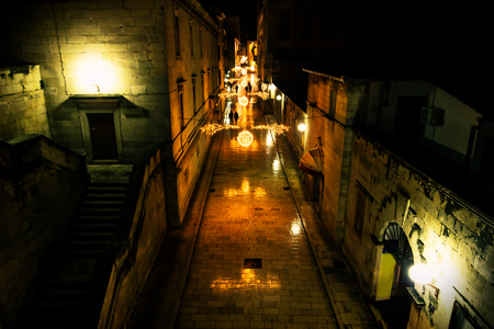 Silhouttes walking along the advent decorated cobbled streets of Zadar at night, Croatia, Europe