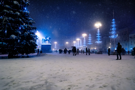 Zagreb main square at night with blue lightened christmas trees during snowing, Croatia Stock Photo