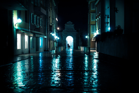 Silhouttes walking through arch on wet old cobbled streets in Zadar, Croatia