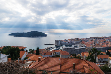 Sunrays coming out of cloudscape over Lokrum Island with aerial view of Dubrovnik, Croatia