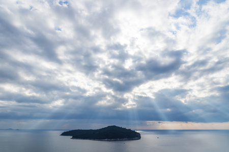 Sunrays coming out of cloudscape over Lokrum Island in front of Dubrovnik, Croatia