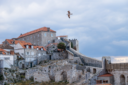 Walkway up to the stone fortress of Durbrovnik with dramatic cloudscape and gull flying over it, Croatia Stock Photo