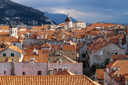View over the sunshined old city Dubrovnik with churches andwith mountains, Croatia Stock Photo