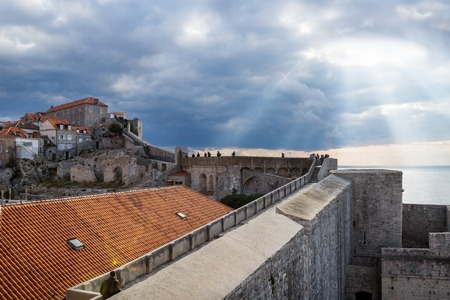 Sunrays shining out of the dramatic cloudscape over stone walls walkway up to the fortress of Durbrovnik, Croatia