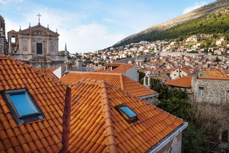 View over the roofs of Dubrovnik and church St. Stepan with bell tower with green mountain in the background, Croatia