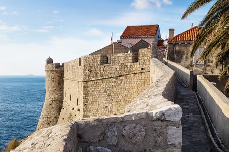 Walkway in sunny weather along the fort of Dubrovnik with lookout and palm tree, Croatia