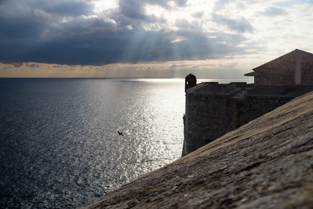 Sunrays out of clouds with watchtower along the fortress of Dubrovnik along the blue ocean, Croatia