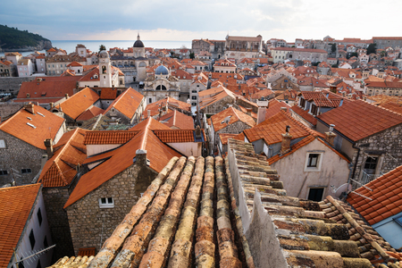Ancient roof with view of old town Dubrovnik with church towers and ocean in winter, Croatia Stock Photo