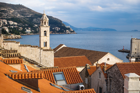 Tower of the Dominican Monastery in front of mountains in Dubrovnik with ocean view, Croatia