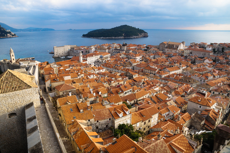 Panorama view of the mediterranean old town of Dubrovnik with orange tiled roofs, walkway on the fortress wall and view on ocean and island Lokrum, Croatia Stock Photo