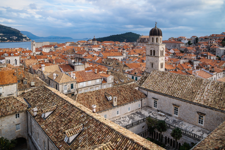 Panorama view of the mediterranean old town of Dubrovnik Franciscan monastery with orange tiled roofs and view on ocean and island Lokrum, Croatia