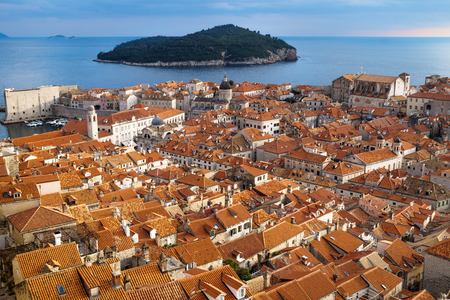 Panorama view of the mediterranean old town of Dubrovnik with orange tiled roofs and view on ocean and island Lokrum, Croatia