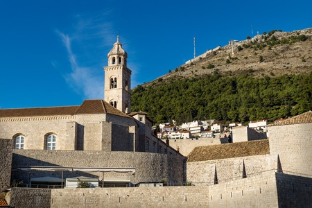 Bell tower of the Dominican Monastery in Dubrovnik with green mountain, Croatia Stock Photo