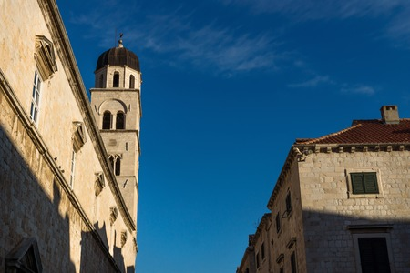 Sunshined tower of St. Saviour church on blue sky in Dubrovnik, Croatia Stock Photo