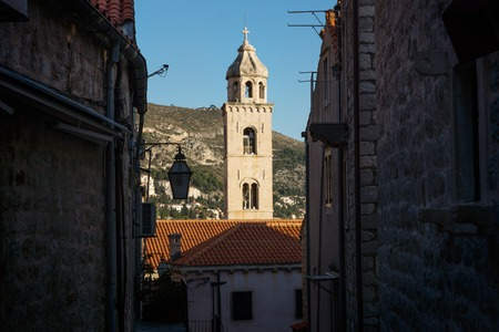 Bell tower of the Dominican Monastery in Dubrovnik seen trough a dark alley, Croatia