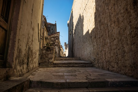 Medieval cobbled street alley with shadows on fortress wall in Dubrovnik, Croatia Stock Photo