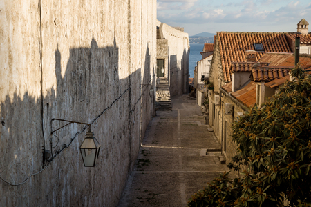 Cobbled street medieval alley in Dubrovnik with view on ocean in winter, Croatia