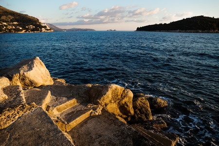 Steps from the port of Dubrovnik into the ocean with view on Lokrum island and coast during sunset, Croatia