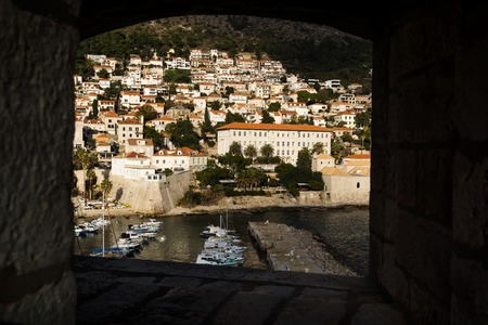 Port of Dubrovnik and houses on mountain seen through a window in the fortress wall, Croatia Stock Photo