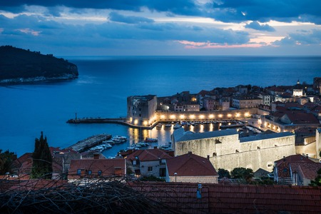 Dubrovnik aerial night view on the harbor after sunset with illuminated fortress wall and dramatic cloudscape, Croatia Stock Photo