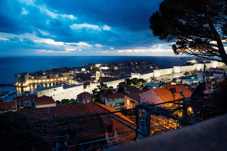 Dubrovnik aerial night view over old town and roofs after sunset with illuminated fortress wall and dramatic cloudscape, Croatia Stock Photo