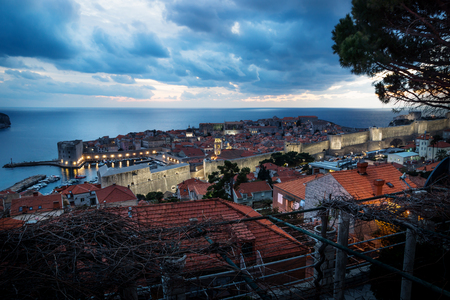 Dubrovnik aerial night view after sunset with illuminated fortress wall and dramatic cloudscape, Croatia Stock Photo