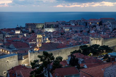 Dubrovnik aerial close up night view after sunset with illuminated fortress wall and dramatic cloudscape, Croatia