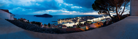 Panorama aerial night view of Dubrovnik, Lokrum Island, roofs and ocean with dramatic cloudscape in winter, Croatia Stock Photo