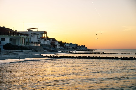Sunset with orange sky along the coast with beach and houses of Chelem, Mexico Stock Photo
