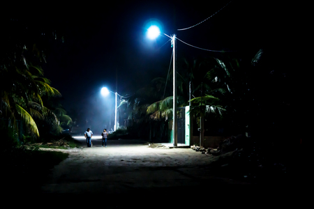Dirtroad in Mexican village in the night with palm trees and silhouttes with blue lamps shining, Chelem, Mexico Stock Photo