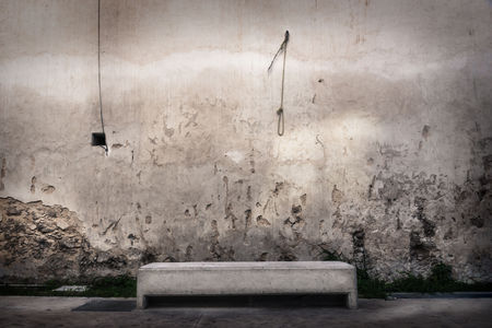 Concrete bench in front of abandoned wall with hangman knot hanging at the wall, Merida, Mexico