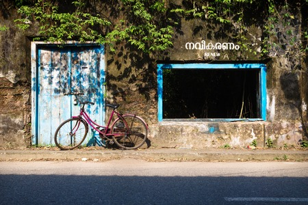 Red bicicle in front of a abandoned building with blue door and window, Kochi, Kerala, India