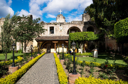 Hermano Pedro garden with green trees and yellow flowers, Antigua, Guatemala Stock Photo - 118920327