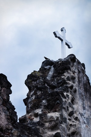 White cross on stone ruins with dramatic blue sky in Hermano Pedro, Antigua, Guatemala
