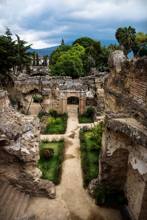 Ruins in Hermano Pedro with green garden and dramatic sky, Antigua, Guatemala