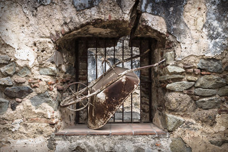 Old wheelbarrow in abandoned window in stone wall, Antigua, Guatemala