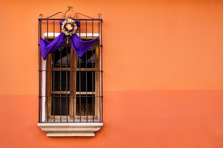 Traditional window on orange wall with purple white semana santa easter ribbon decoration in Antigua, Guatemala