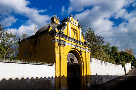 Yellow chapel church with crooked cross under blue cloud sky, Antigua, Guatemala