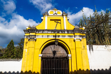 Yellow chapel church fasade with crooked cross under blue cloud sky, Antigua, Guatemala