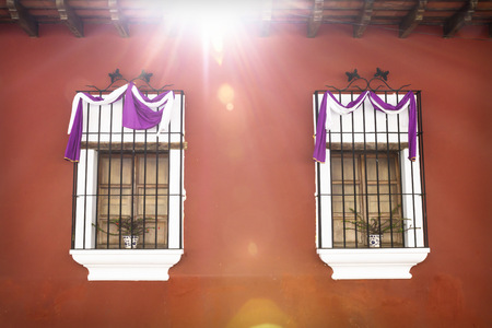 Two traditional windows with purple white semana santa easter ribbon decoration and sunbeam in Antigua, Guatemala