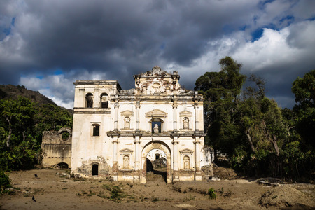 Church fasade ruin under dramatic blue cloudscape, Antigua, Guatemala