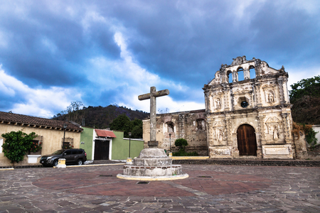 Church fassade ruin of Ermita de Santa Isabel and cross on plazawith dramatic blue cloudscape, Antigua, Guatemala